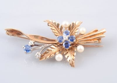 A Sapphire, Diamond and Gold Spray Brooch, circa 1950. £300.