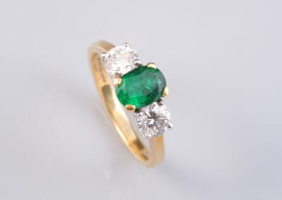 A Three Stone Emerald and Diamond Ring, Set in 18 Carat Gold. £2,500.