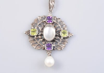 An Arts and Crafts Amethyst, Peridot, Pearl and Silver Necklace, circa 1900. £600.