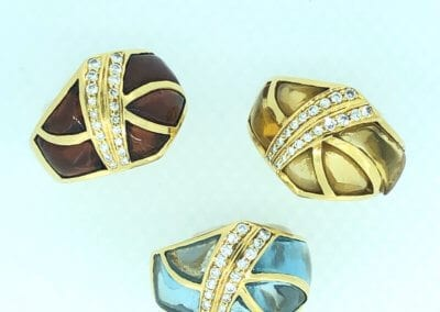 A trio of 18 Carat Yellow Gold Cocktail Rings by Dianoor - Citrine, Garnet & Blue Topaz with Diamonds - £650 each